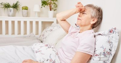 Woman with headache laying in bed